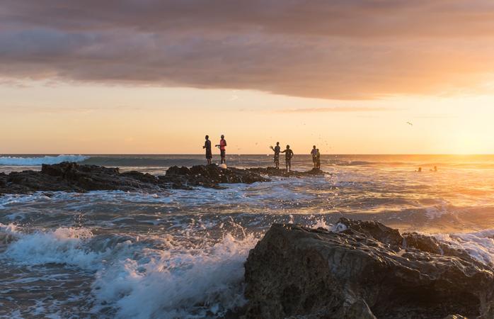 Eine Gruppe Angler versucht, exotische Fische an der felsigen Küste zu fangen.