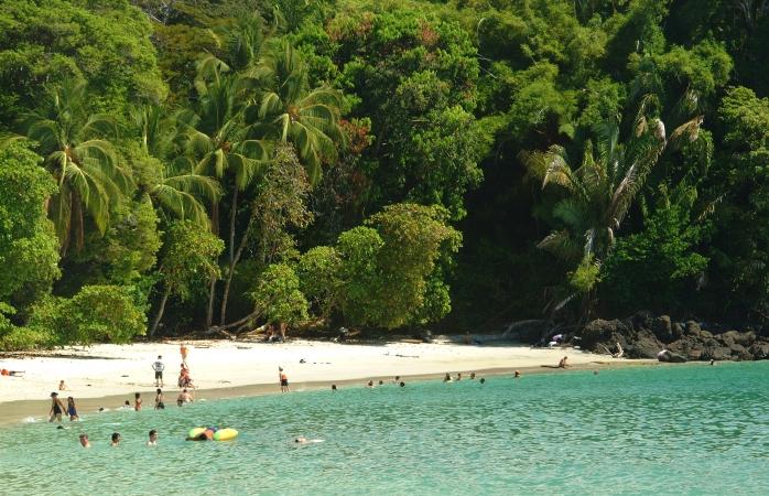 Eine kleine Gruppe Sonnenanbeter faulenzt und schwimmt am Playa Manuel Antonio, Costa Rica.